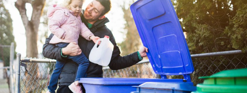 A dad holds his daughter as he teaches her about the environmentally friendly practice of recycling plastic and cardboard waste.  A good practical learning opportunity.